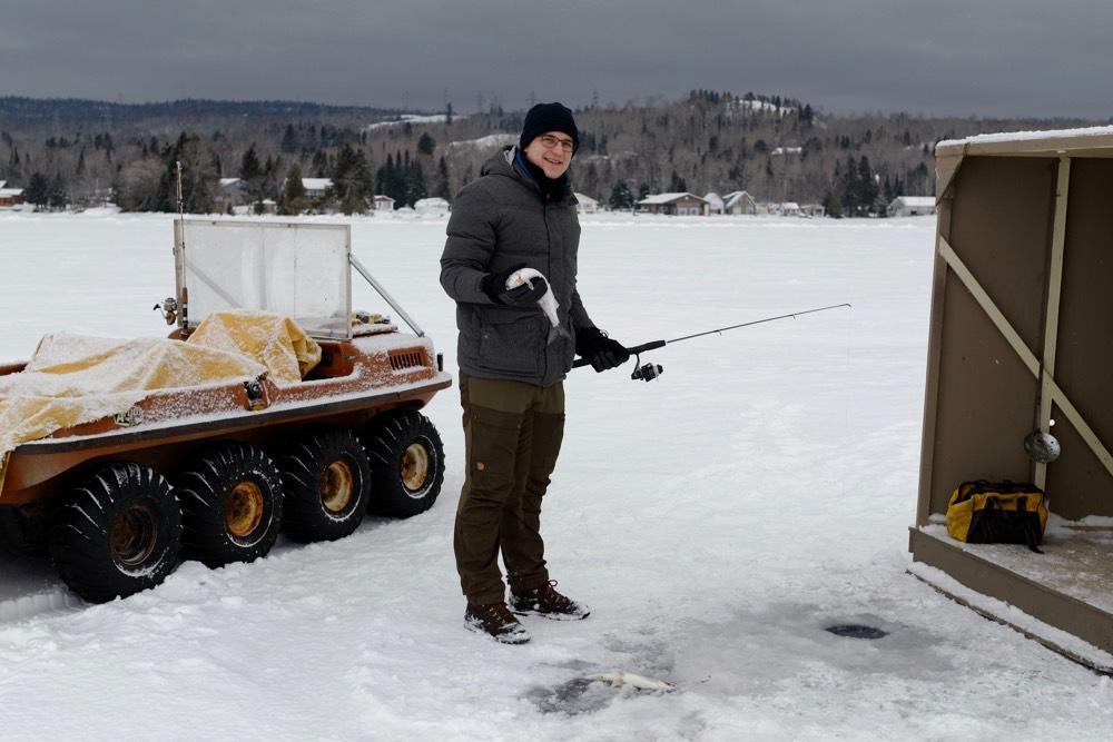 Ich stehe auf einem zugefrorenen See mit einer ANgel und einem FIsch in den Händen.