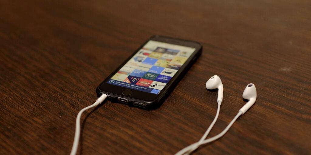 Ein Smartphone mit geöffneter Podcast-App liegt mit Kopfhörern auf einem Holztisch.