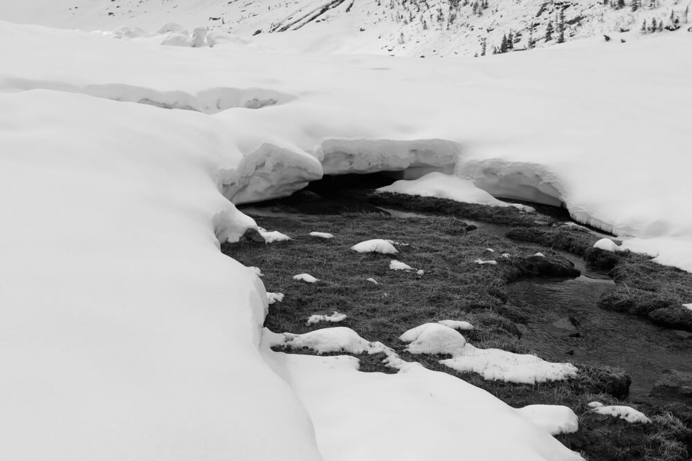 Eine etwa ein Meter dicke Schneeschicht formt eine Brücke über einen Bach.