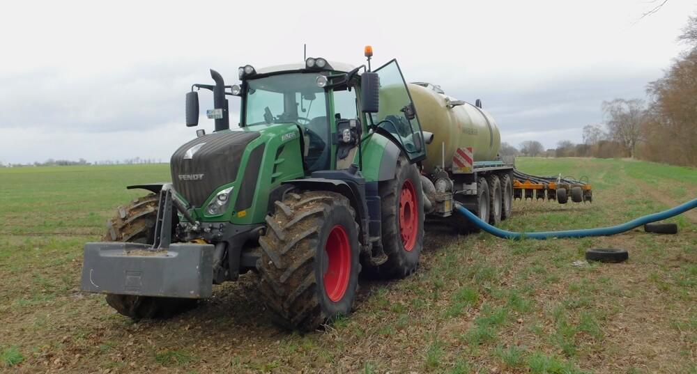 Ein Traktor mit angehängtem Güllefass steht auf einem Feld.